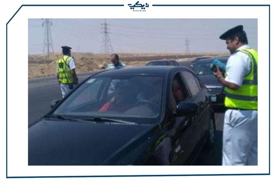 رجل مرور يدون مخالفة على قائد سيارة